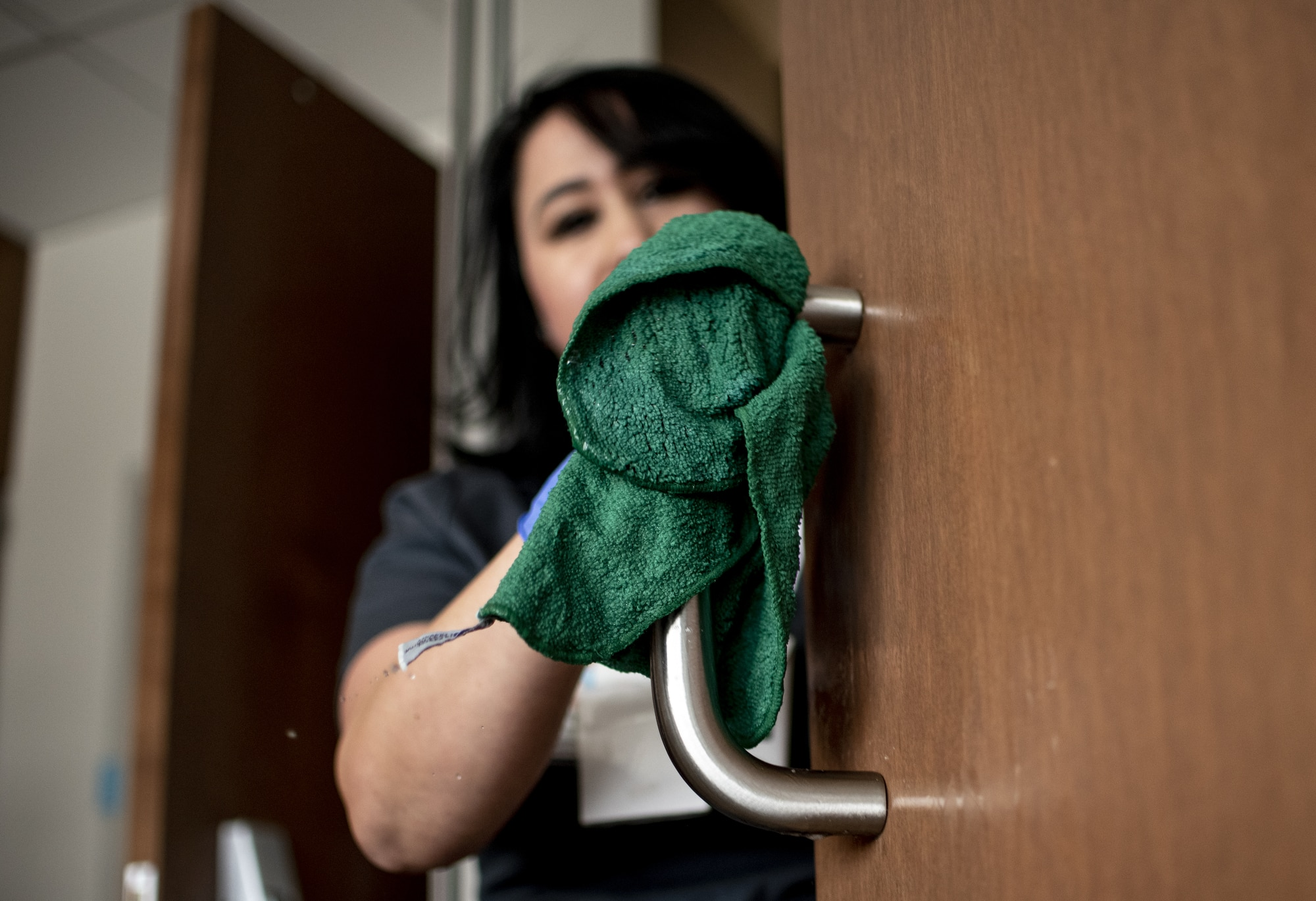 lady cleaning handle of wooden door with a rag