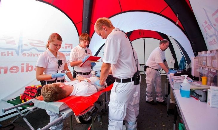 Emergency personnel care for a patient inside an inflatable medical tent.