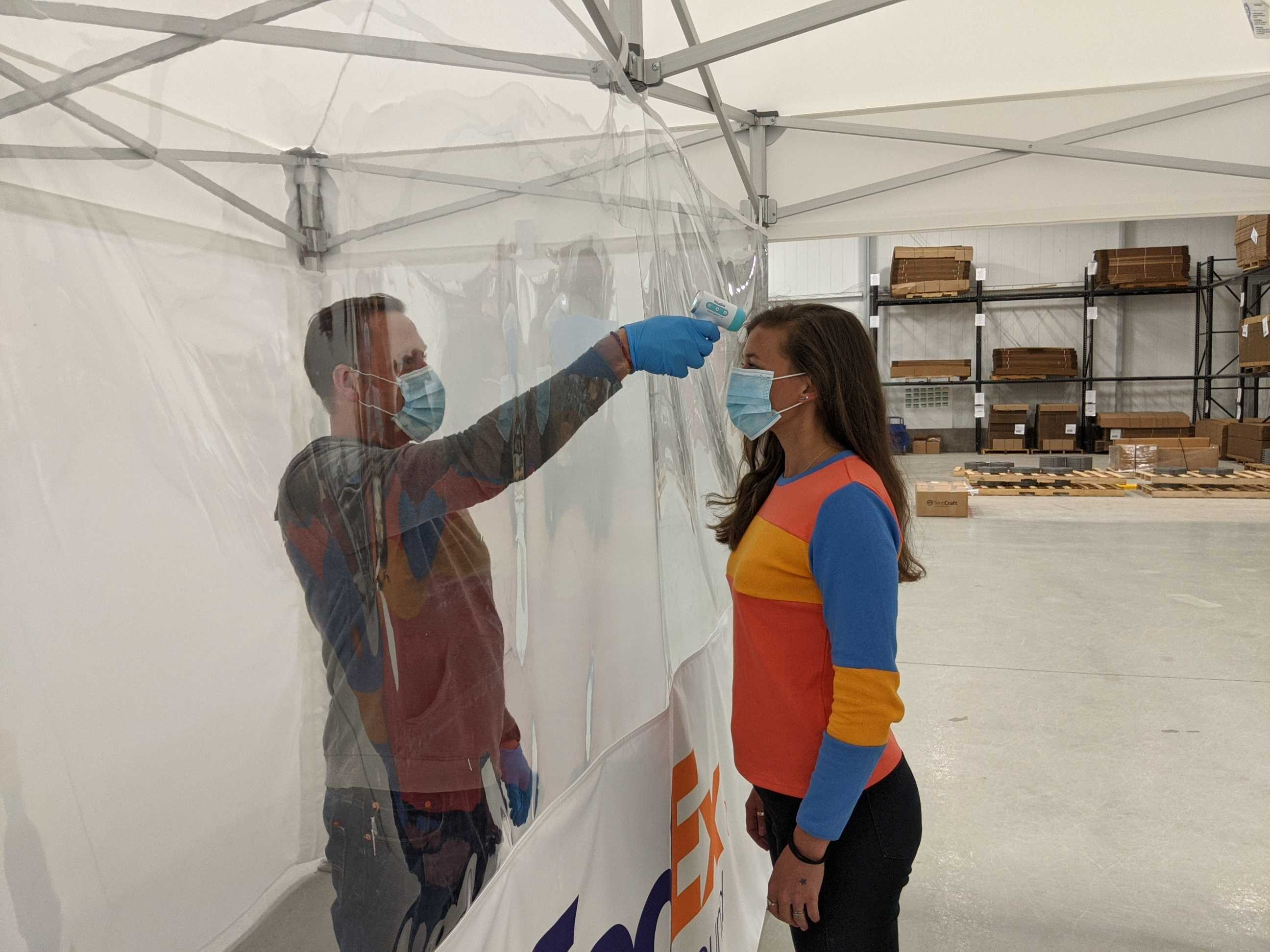 employee temperature screening happening inside of a popuptent with vinyl seperator