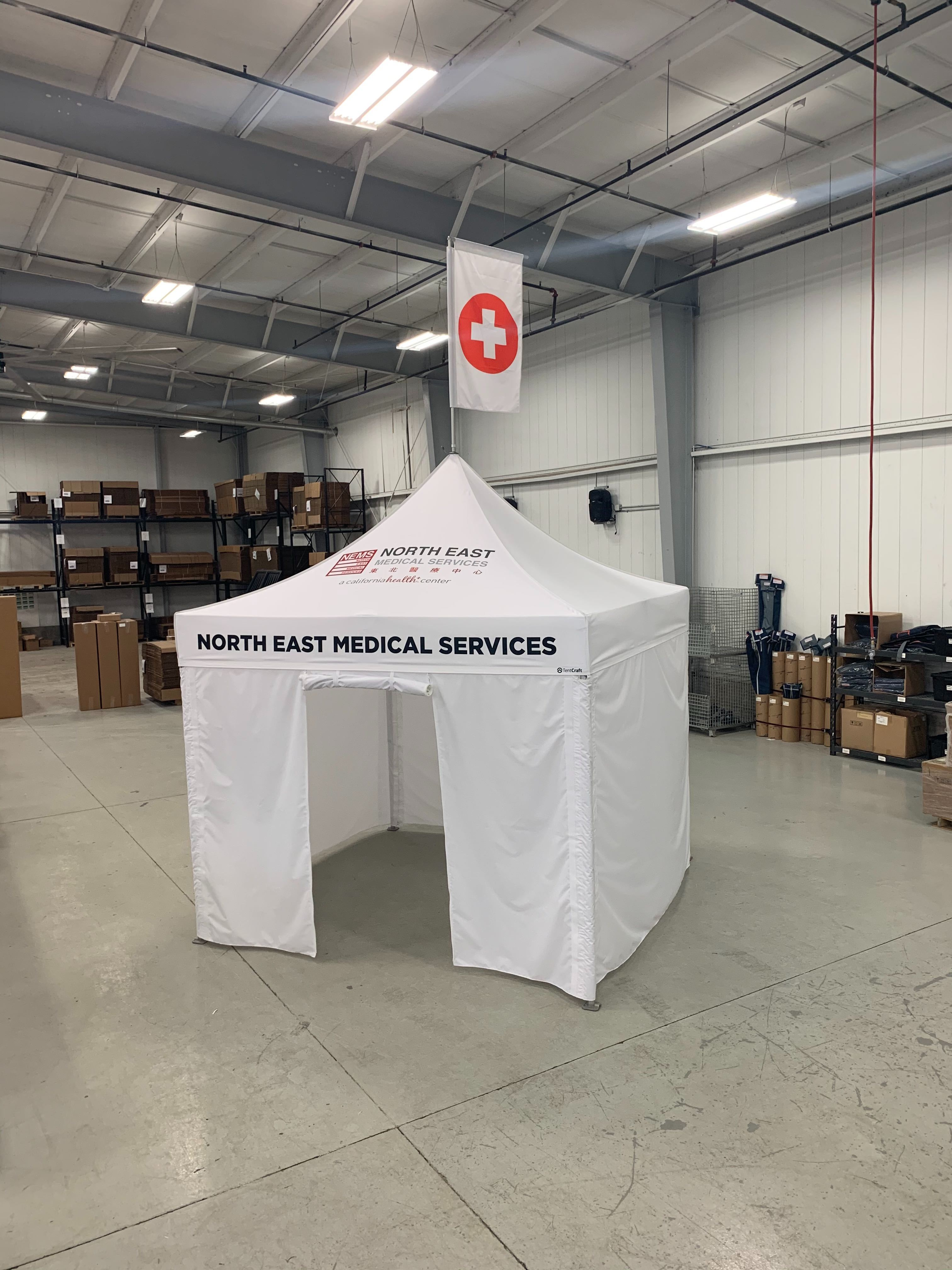 White 10x10 medical tent with roll-up entryway and custom printed canopy and peak flag